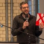 """Matthias Böttger, künstlerischer Leiter des DAZ, weist auf Ausstellung und Katalog """"Neue Standards. Zehn Thesen zum Wohnen"""" hin, Foto: Till Budde"""
